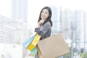 たくさんの買い物袋を抱える女性の写真素材 [FYI04830409]