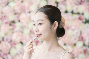 化粧(口紅)・女性・フラワー背景の写真素材 [FYI04830540]