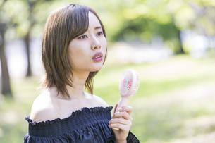 携帯型の扇風機で涼む女性の写真素材 [FYI04830565]