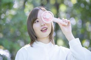 携帯型の扇風機で涼む女性の写真素材 [FYI04830570]