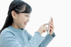 スマートフォンを操作する女の子の写真素材 [FYI04830780]