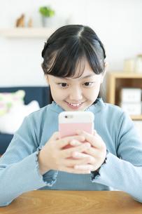 スマートフォンを見る女の子の写真素材 [FYI04830781]