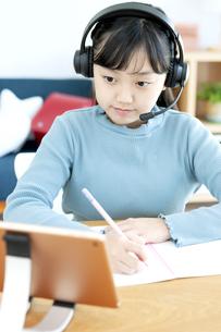 インカムをつけてタブレットで勉強する女の子の写真素材 [FYI04830794]