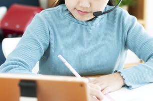 インカムをつけてタブレットで勉強する女の子の写真素材 [FYI04830795]