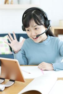 インカムをつけてタブレットで勉強する女の子の写真素材 [FYI04830796]