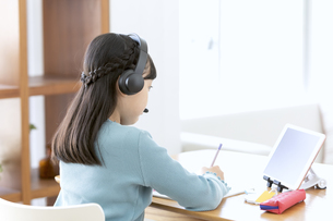 インカムをつけてタブレットで勉強する女の子の写真素材 [FYI04830803]