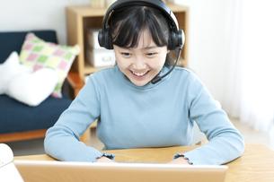 インカムをつけてパソコンする女の子の写真素材 [FYI04830806]