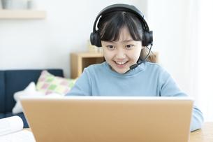 インカムをつけてパソコンする女の子の写真素材 [FYI04830807]