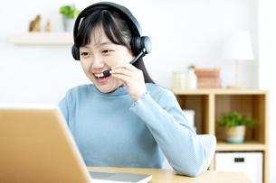 インカムをつけてパソコンする女の子の写真素材 [FYI04830809]
