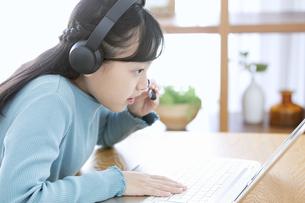インカムをつけてパソコンする女の子の写真素材 [FYI04830813]
