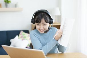 インカムをつけて勉強する女の子の写真素材 [FYI04830815]
