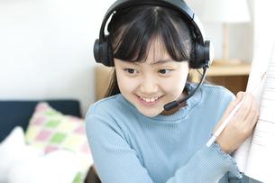 インカムをつけて勉強する女の子の写真素材 [FYI04830818]