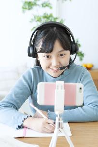 インカムをつけて勉強する女の子の写真素材 [FYI04830819]