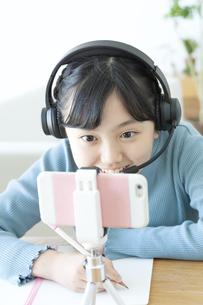 インカムをつけて勉強する女の子の写真素材 [FYI04830821]