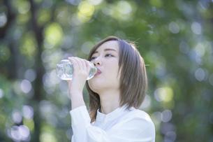 公園で水を飲む女性の写真素材 [FYI04831228]