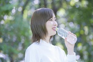 公園で水を飲む女性の写真素材 [FYI04831230]