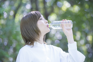 公園で水を飲む女性の写真素材 [FYI04831232]