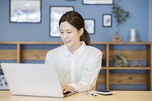 カジュアルな部屋で仕事をする女性の写真素材 [FYI04831240]