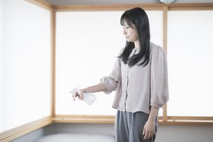 スプレーで部屋を消毒・殺菌する女性の写真素材 [FYI04831252]
