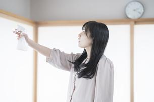 スプレーで部屋を消毒・殺菌する女性の写真素材 [FYI04831253]