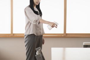 スプレーで部屋を消毒・殺菌する女性の写真素材 [FYI04831255]