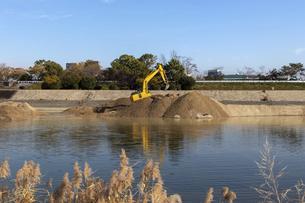 川岸で工事を行う油圧ショベルの写真素材 [FYI04831567]