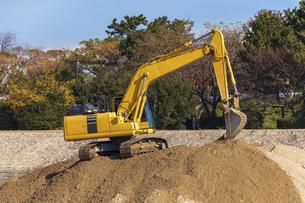 砂山の上で作業をする油圧ショベルの写真素材 [FYI04831568]