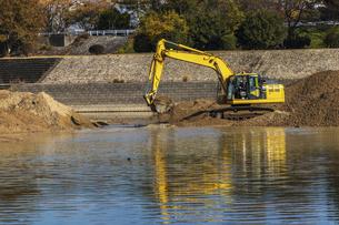川岸で工事を行う油圧ショベルの写真素材 [FYI04831569]