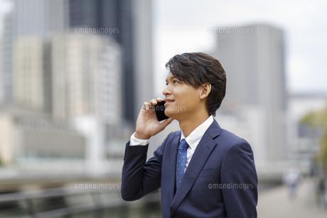 スマートフォンで話すビジネスマンの写真素材 [FYI04831991]