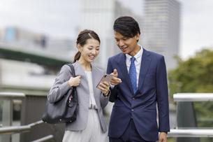 スマートフォンを見るビジネス男女の写真素材 [FYI04831994]