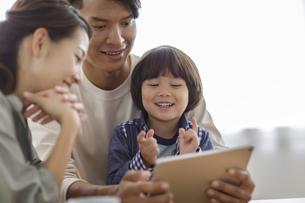 タブレットPCを見る日本人家族の写真素材 [FYI04832015]