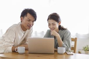 ノートパソコンを見る日本人夫婦の写真素材 [FYI04832020]
