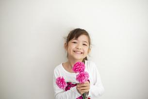 カーネーションを持って笑っている女の子の写真素材 [FYI04832801]