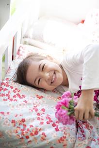 カーネーションを持ってベッドに寝転がっている女の子の写真素材 [FYI04832805]
