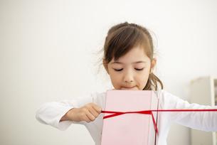 箱にリボンを結んでいる女の子の写真素材 [FYI04832819]