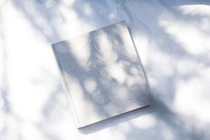 自然光と植物の影が差し込む、白のファブリックに置かれた本の写真素材 [FYI04832956]