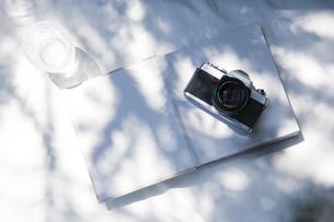自然光と植物の影が差し込む、白のファブリックに置かれた本の写真素材 [FYI04832961]