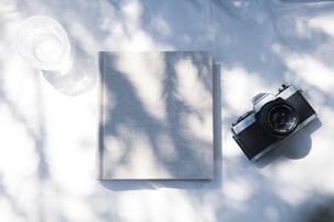 自然光と植物の影が差し込む、白のファブリックに置かれた本の写真素材 [FYI04832962]