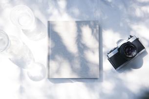 自然光と植物の影が差し込む、白のファブリックに置かれた本の写真素材 [FYI04832963]