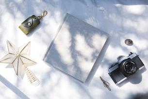 自然光と植物の影が差し込む、白のファブリックに置かれた本の写真素材 [FYI04832965]