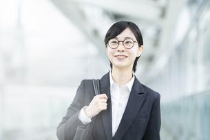 スーツ姿で笑顔を見せる若い女性の写真素材 [FYI04833073]