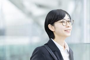 スーツ姿で笑顔を見せる若い女性の写真素材 [FYI04833078]