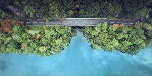 ドローンで撮影した俯瞰で見た森と道路と海の写真素材 [FYI04833259]