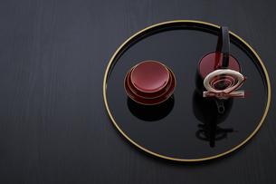 黒バックで金縁の丸盆に乗ったお屠蘇の酒器と杯の写真素材 [FYI04833775]