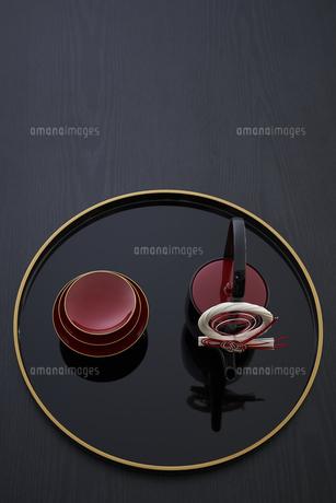 黒バックで金縁の丸盆に乗ったお屠蘇の酒器と杯の写真素材 [FYI04833776]