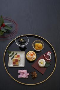 黒バックで金縁の丸盆に乗った小鉢の料理と赤い水引と千両の写真素材 [FYI04833778]