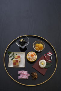 黒バックで金縁の丸盆に乗った小鉢の料理の写真素材 [FYI04833779]