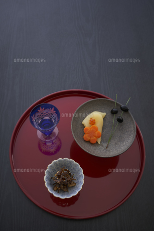 赤い丸盆に乗った切子グラスと小鉢に入った料理の写真素材 [FYI04833783]