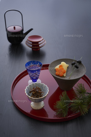 赤い丸盆に乗った切子グラスと小鉢に入った料理とお屠蘇セットの写真素材 [FYI04833784]