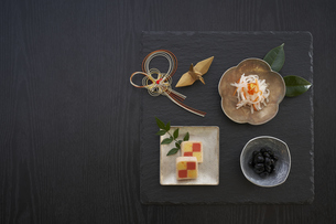 黒の石板に乗った小鉢の料理と水引の正月飾りと金色の鶴の写真素材 [FYI04833785]